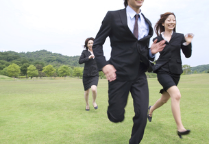 草原を走るビジネスマンとビジネスウーマンの素材 [FYI01143556]