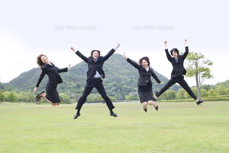 草原でジャンプをするビジネスマンとビジネスウーマンの素材 [FYI01143570]