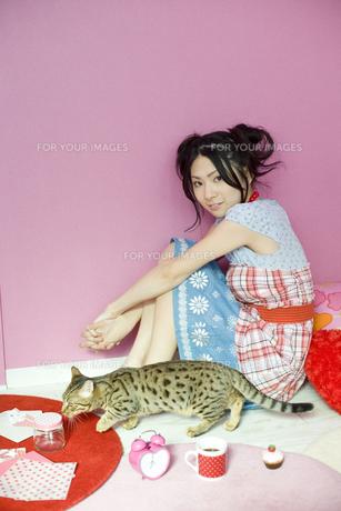 ピンクの雑貨に囲まれた女性と猫の素材 [FYI01143571]