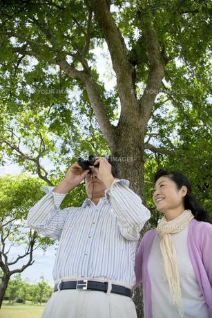 双眼鏡を覗くシニア男性と女性の素材 [FYI01143594]