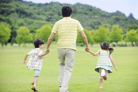 草原を手をつないで走る親子の後ろ姿の素材 [FYI01143607]