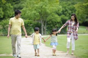 草原を手をつないで歩く家族の素材 [FYI01143622]