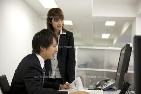 パソコンの画面を見つめるビジネスマンとOLの素材 [FYI01143638]