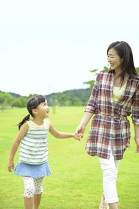 草原を手をつないで歩く親子の素材 [FYI01143639]