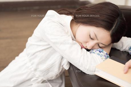 ソファにもたれうたた寝をする女性の素材 [FYI01143722]