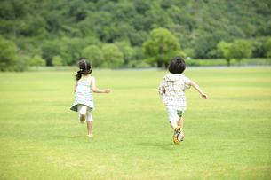 草原を走る子供達の後ろ姿の素材 [FYI01143758]