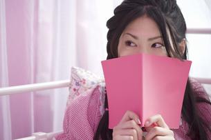 ピンクのノートで顔を隠した女性の素材 [FYI01143824]