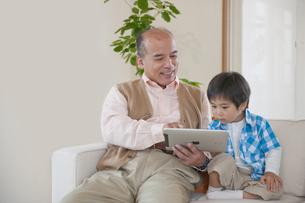 ソファに座るおじいちゃんと男の子の素材 [FYI01143850]