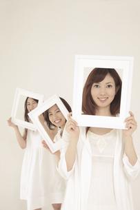 白い額縁から顔を覗かせる3人の女性の素材 [FYI01143880]