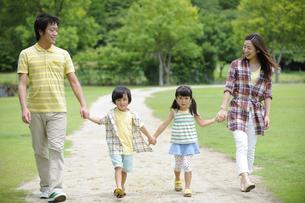草原を手をつないで歩く家族の素材 [FYI01143924]