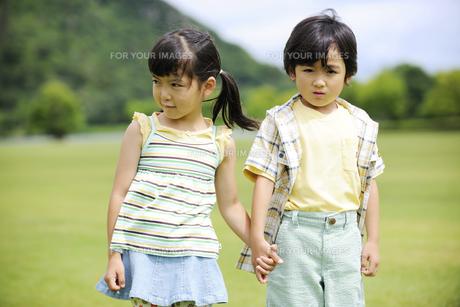 草原で手をつなぐ兄妹の素材 [FYI01144105]