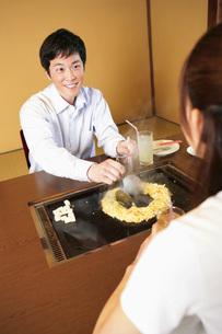 もんじゃ焼きを食べるカップルの素材 [FYI01152538]