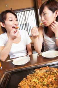 もんじゃ焼きを食べる女性の素材 [FYI01152583]