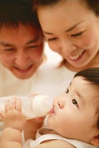 ミルクを飲む赤ちゃんと父と母の素材 [FYI01152792]