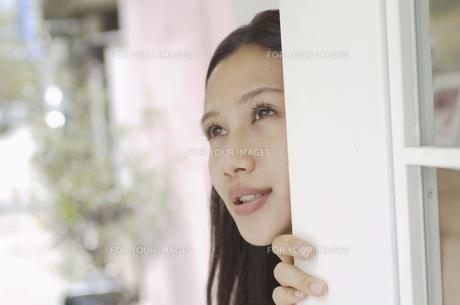 扉から顔を出す女性の素材 [FYI01156831]