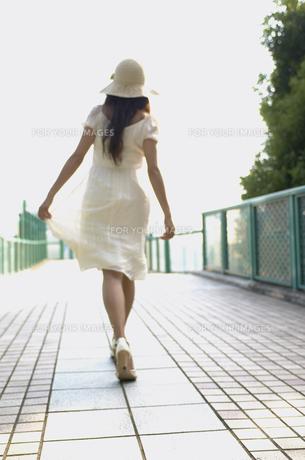 帽子をかぶって歩く女性の後姿の素材 [FYI01156955]
