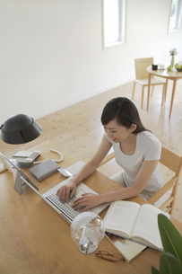 部屋でパソコンを使う女性の素材 [FYI01156965]