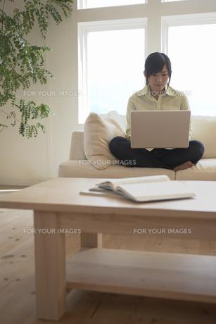 ソファに座り、パソコンを使う女性の素材 [FYI01156978]