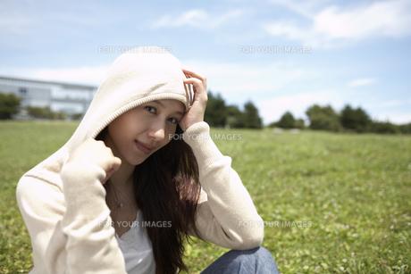 草むらに座る帽子をかぶった女性の素材 [FYI01156985]