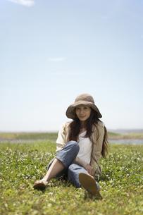 草むらに座る帽子をかぶった女性の素材 [FYI01157004]