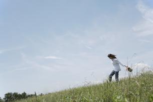 草むらを歩く女性の素材 [FYI01157073]