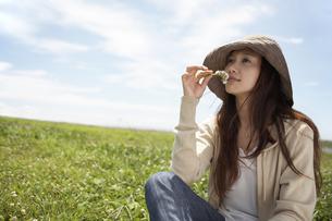 花の匂いをかぐ帽子をかぶった女性の素材 [FYI01157161]