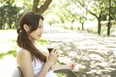 公園のベンチに座る女性の素材 [FYI01157172]