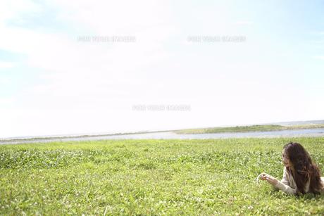 草むらに寝転ぶ女性の素材 [FYI01157308]