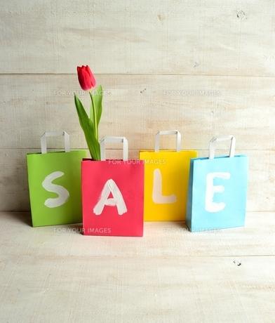 赤いチューリップが入ったパステルカラーのショッピングバッグ セール文字入りの写真素材 [FYI01158765]