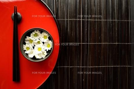 赤いおぼんの上の箸と小鉢にいけた小菊の写真素材 [FYI01158799]