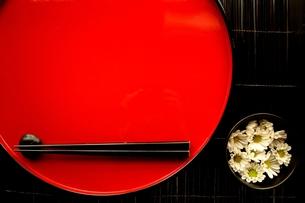 赤いおぼんと箸と小鉢にいけた小菊の写真素材 [FYI01158812]