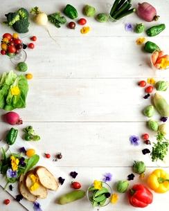 野菜とエディブルフラワーとパン  白木材背景の写真素材 [FYI01158831]
