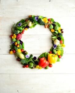 野菜とエディブルフラワーのリース 白木材背景の写真素材 [FYI01158833]
