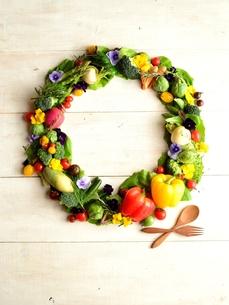 野菜とエディブルフラワーと木製スプーンとフォークのリース 白木材背景の写真素材 [FYI01158835]