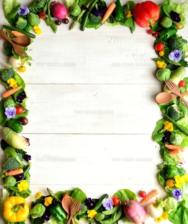 野菜とエディブルフラワーと木製スプーンとフォーク 白木材背景の写真素材 [FYI01158837]