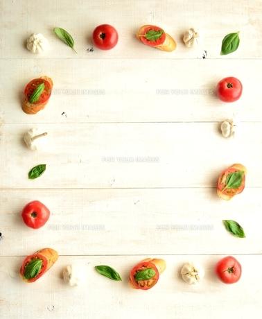 トマトのブルスケッタとにんにくとバジルリーフ 白木材背景の写真素材 [FYI01158847]