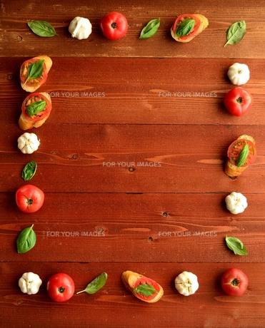 トマトのブルスケッタとにんにくとバジルリーフ 茶色木材背景の写真素材 [FYI01158851]
