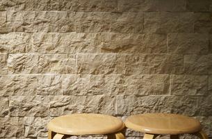 灯かりに照らされた壁と丸椅子の写真素材 [FYI01159544]