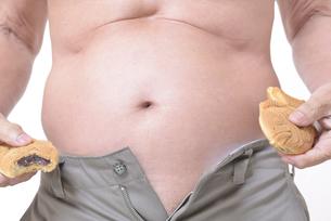 肥満体シニアたい焼きを食べるの写真素材 [FYI01160423]