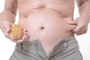 肥満体シニアたい焼きを食べるの写真素材 [FYI01160426]