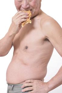 肥満体シニアたい焼きを食べるの写真素材 [FYI01160431]