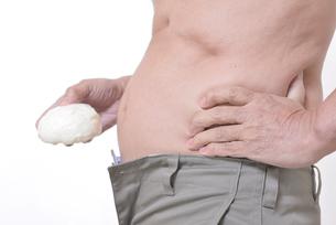 肥満体シニア肉まんを食べるの写真素材 [FYI01160436]