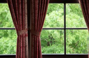部屋のカーテンと窓から見える緑の写真素材 [FYI01160494]