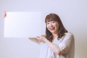 ホワイトボードを持つ若い女性の写真素材 [FYI01162643]