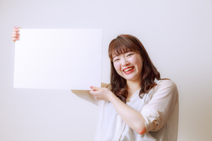 ホワイトボードを持つ若い女性の写真素材 [FYI01162644]