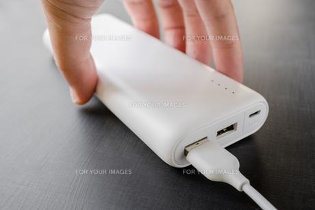 モバイルバッテリーを持つ手の写真素材 [FYI01162827]