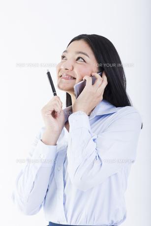 電話をしながら考え事をする女性の写真素材 [FYI01163443]