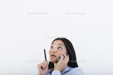 電話をしながら考え事をする女性の写真素材 [FYI01163453]