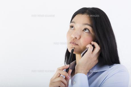 電話をしながら考え事をする女性の写真素材 [FYI01163456]