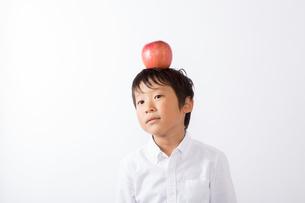 りんごを頭にのせる少年の写真素材 [FYI01163913]
